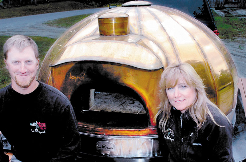 MOBILE HEAT: Scott and Cheryl Barden beside a mobile oven that they assemble and sell at their Maine Wood Heat. The former Norridgewock company has relocated to the Northgate Industrial Park in Skowhegan.