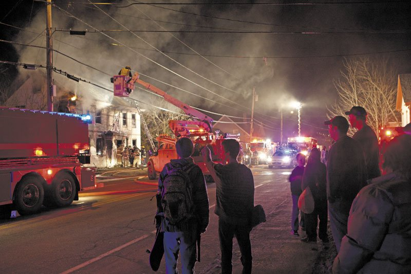 Bystanders watch firefighters attempt to douse a fire in Randolph Saturday night. The fire restarted Sunday morning. Officials suspect the fire was set.