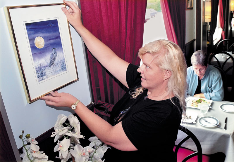 Kiri Guyaz hangs one of her paintings among diners at the M. Thai restaurant in Skowhegan. The venue is one of several taking part in the Wesserunsett Arts Council and Main Street Skowhegan sponsored art walk, beginning this Friday and running through the summer.