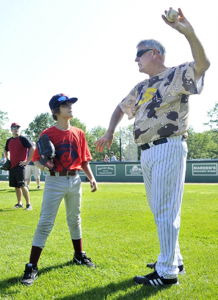 TEACHING THE GAME: Former Major League Baseball pitcher Tommy John offers some pitching tips to Wyatt Viles, 10, of Strong, during a baseball academy Monday morning at Harold Alfond Fenway Park in Oakland. John, famous for the surgery performed on his left elbow, pitched 26 seasons in the majors.