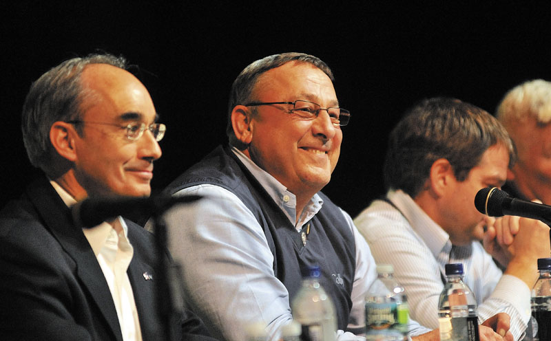 TOWN HALL: Gov. Paul LePage, center, takes questions from the audience Thursday night during a town hall-style meeting at Mount View High School in Thorndike Thursday. The event was part of his continuing Capitol for a Day tour of the state. Seated next to Gov. LePage is state treasurer Bruce Poliquin.