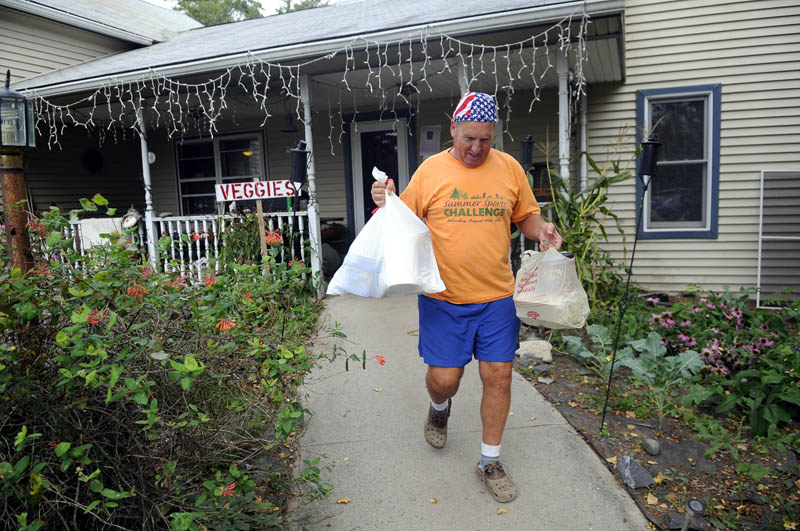 SPECIAL DELIVERY: Volunteer Stephen Dodge carries meals from Annabessacook Farm in Winthrop. Dodge — a Wayne resident who coordinates the kitchen — said he could take a $1 donation and parlay it into food worth three or four times that much.