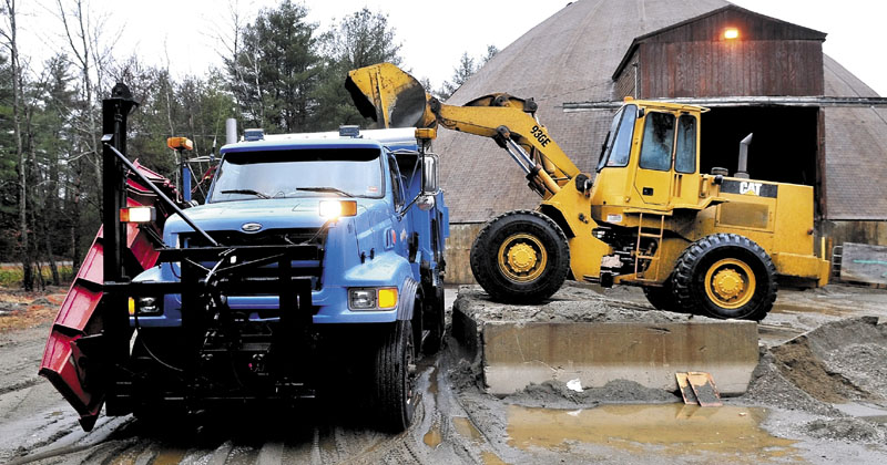 FILL 'ER UP: Willy Marsh loads salt and sand into a Skowhegan Highway Department plow truck on Thursday. The department will be using a road de-icer product called Ice B Gone made of high-sugar beet molasses that is less corrosive on the environment and vehicles.