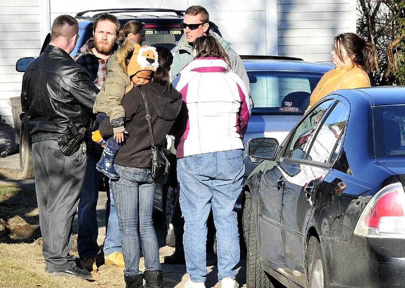 LOOKING FOR CLUES: Maine State Police Detective Christopher Tupper, left, talks to Justin DiPietro on Dec. 18 at his home on Violette Avenue in Waterville. His daughter, 20-month-old Ayla Reynolds, has been missing since Dec. 17.