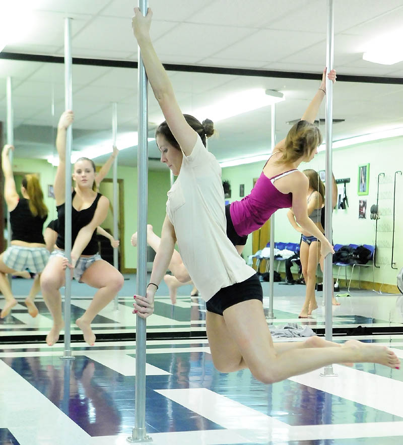 Sarah Stetson, left, Molly Hendsbee and Tammy Poulin hang off their pole during a pole fitness class on Wednesday night at Heaven-Lee Heights Inc. at 553 Maine Ave., Farmingdale.