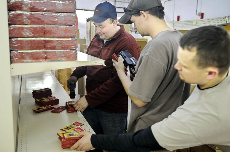 Nick Hamel, right, Selby Landmann, center, and Scott Boucher price firecrackers recently at Pyro City Fireworks on Route 202 in Manchester. Employees stocked up for the Thursday opening of the first fireworks store in Maine since the ban on fireworks was lifted last year.