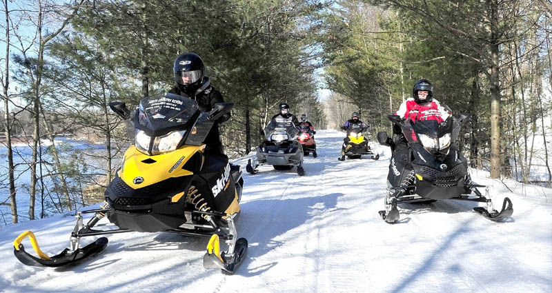 Scott Newton, left, of North Country Rivers in Bingham, leads snowmobilers down Interconnected Trail System ITS 87 recently. Low snow amounts are beginning to pick up, and the company is counting on improving snow conditions for the rest of February and March snowmobile rental business.