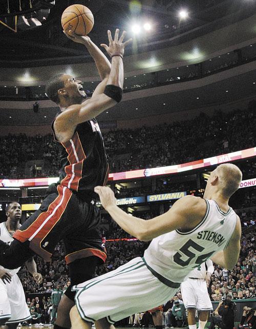 CHARGE: Boston Celtics center Greg Stiemsma (54) draws an offensive foul on Miami Heat power forward Chris Bosh in the first half Sunday in Boston.