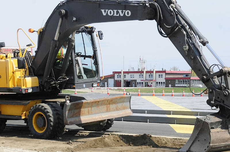 RUNWAY WORK: The Augusta State Airport terminal is framed by an excavator working Friday on the end of the closed main runway.