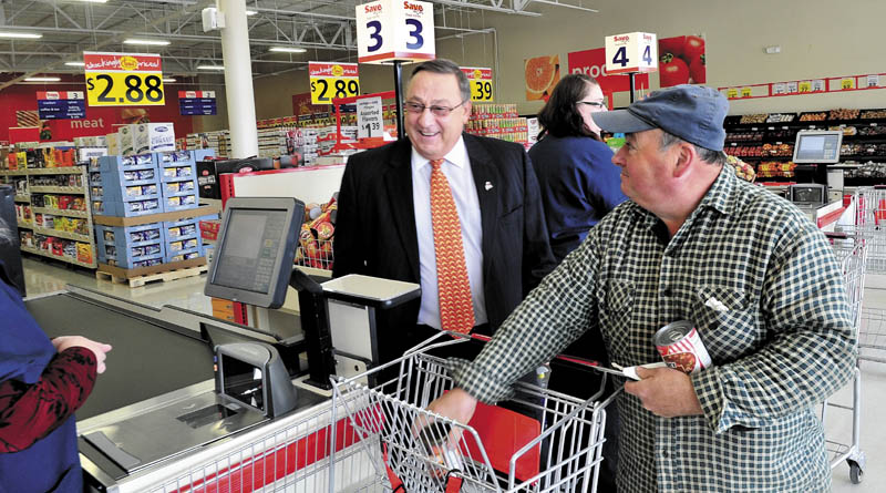 CHECK IT OUT: Gov. Paul LePage tours the new Save-A-Lot grocery store that opened Wednesday in The Concourse in Waterville as customer John Roy's groceries are rung up by a cashier.