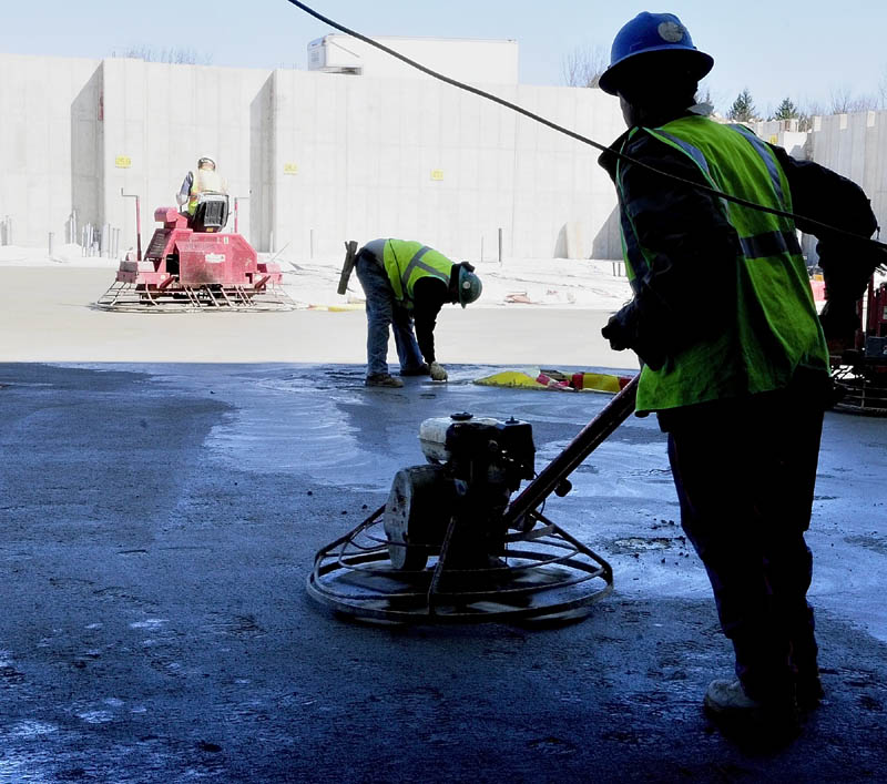Workers from Newman Concrete Services, Inc. in Richmond, finish recently poured concrete last week at the new MaineGeneral regional hospital being built in Augusta.