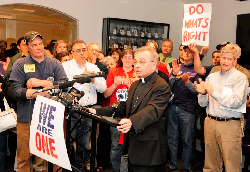 People cheer as the Rev. Mike Seavey, a Catholic priest, speaks during a news conference held by opponents of L.D. 309 in the State House on Wednesday in Augusta. The so-called right-to-work bill was to come up for a vote by a legislative committee.