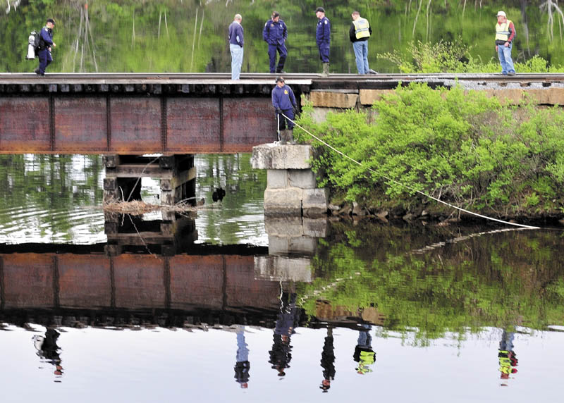SEARCH: Maine State Police divers search Martin Stream near the Kennebec River off U.S. Route 201 in Hinckley on Sunday.