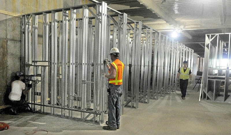 Workers are prefabricating the walls behind patient beds with wiring and piping before they're installed upstairs at MaineGeneral's new regional hospital under construction in North Augusta.