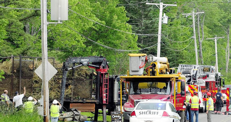 Investigators look over the logging truck where a man was electrocuted this afternoon on Spears Corner Road in West Gardiner.