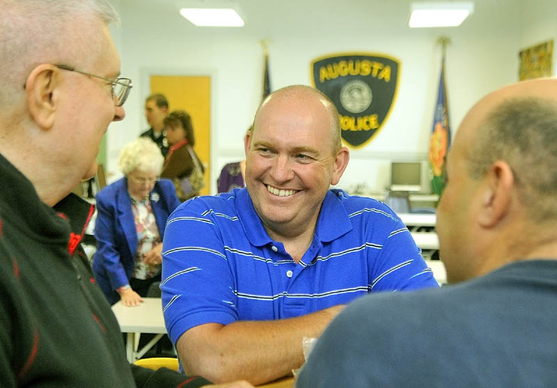 Retiring Augusta Police patrolman Lindell Cox, center, chats with department chaplain Don Williams, left, and Sgt. Richard Dubois on Wednesday morning at his retirement party in Augusta.