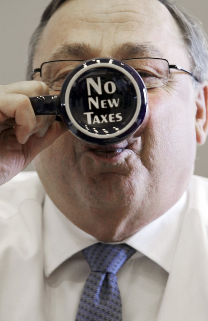 Gov. Paul LePage sips from a coffee mug displaying a message on the bottom in his office at the State House in Augusta in April.