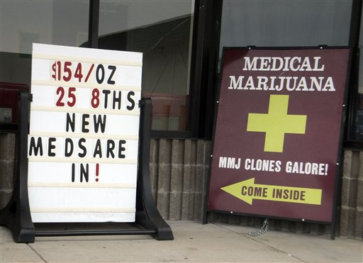 Sidewalk ads outside a west Denver medical marijuana dispensary advertise low prices and