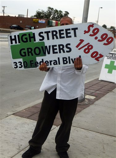 A sign-spinner outside a west Denver medical marijuana dispensary advertises low-cost pot as rush hour drivers pass the pot shop on Monday.