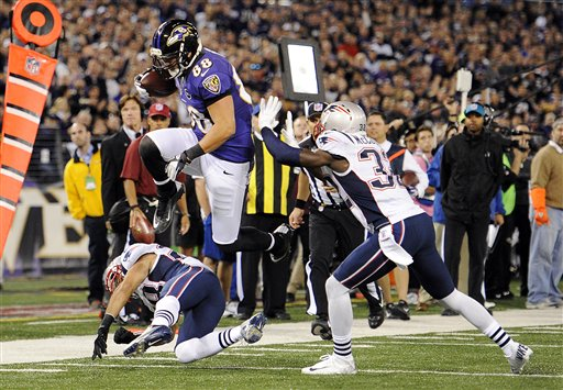 GETTING BY: Baltimore Ravens tight end Dennis Pitta (88) leaps past New England Patriots defenders Steve Gregory, bottom left, and Devin McCourty before scoring a touchdown in the first half Sunday night in Baltimore.