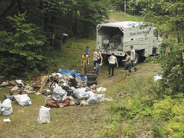 A group of young men and women pick up trash Saturday at an illegal dump site off Chesterville Ridge Road in Fayette. A group of roughly 20 teens and young adults, all of whom were charged in connection with an underage drinking party last month in Wayne, took part in the first ever Landowner Appreciation Clean-up Day. The group spent eight hours picking up trash in Fayette and Augusta in lieu of appearing in court. All of those pictured are 18 or older.