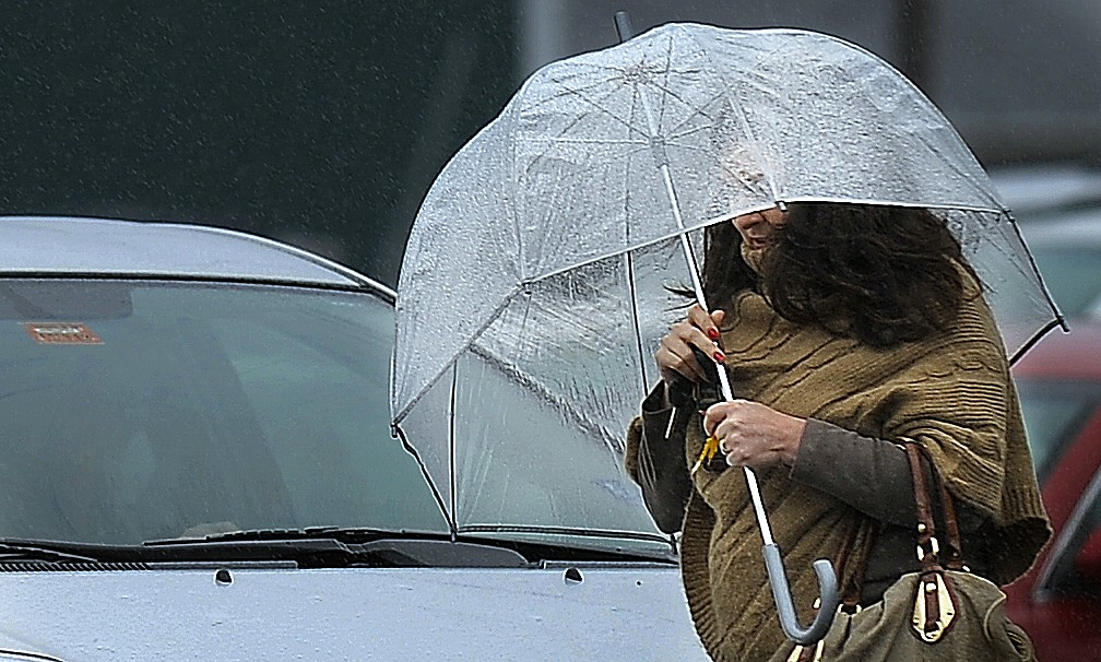 Laura Gough of Cape Elizabeth shields herself with an umbrella as she walks to work on Commercial Street Monday morning, October 29, 2012.