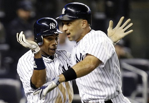 New York Yankees' Curtis Granderson, left, celebrates with Raul Ibanez after scoring on Ibanez's ninth-inning, two-run home run during their baseball game against the Boston Red Sox at Yankee Stadium in New York, Tuesday, Oct. 2, 2012. The Yankees won 4-3 in the 12th inning. (AP Photo/Kathy Willens)