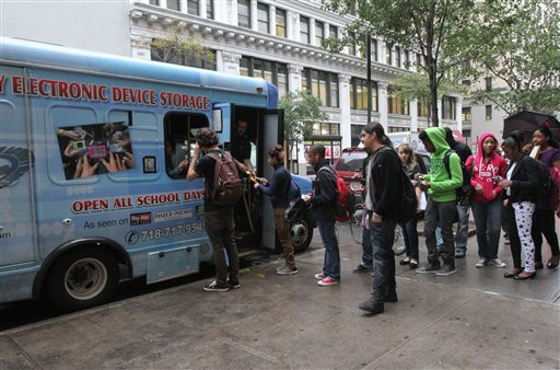 Students from New York's Washington Irving educational complex line up last week to leave their cellphones and other electronic devices, for a dollar a day per item, in a privately operated truck parked near their school.