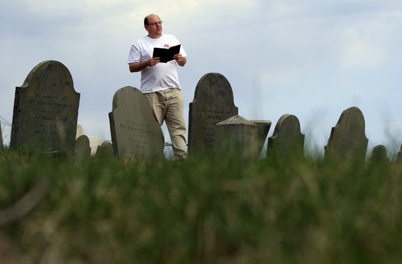 Walter Skold of Freeport reads a Henry Wadsworth Longfellow poem in Portland's Eastern Cemetery in this April 20, 2010, photo.