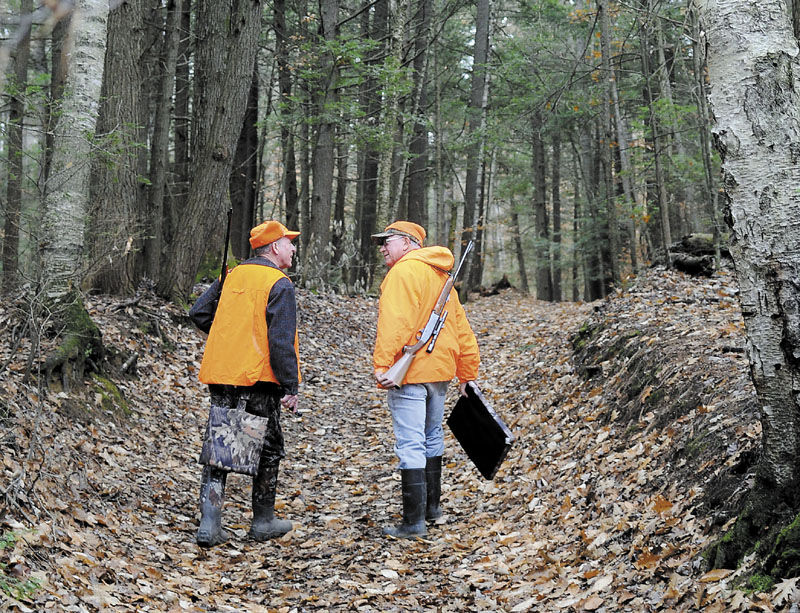 Bill Moulton, right, of Pittston, chats with his pal, Gary Alexander, of Gardiner, as they walk down a path in a wood in South Gardiner in pursuit of whitetail deer last season. Moulton said the men have been hunting together