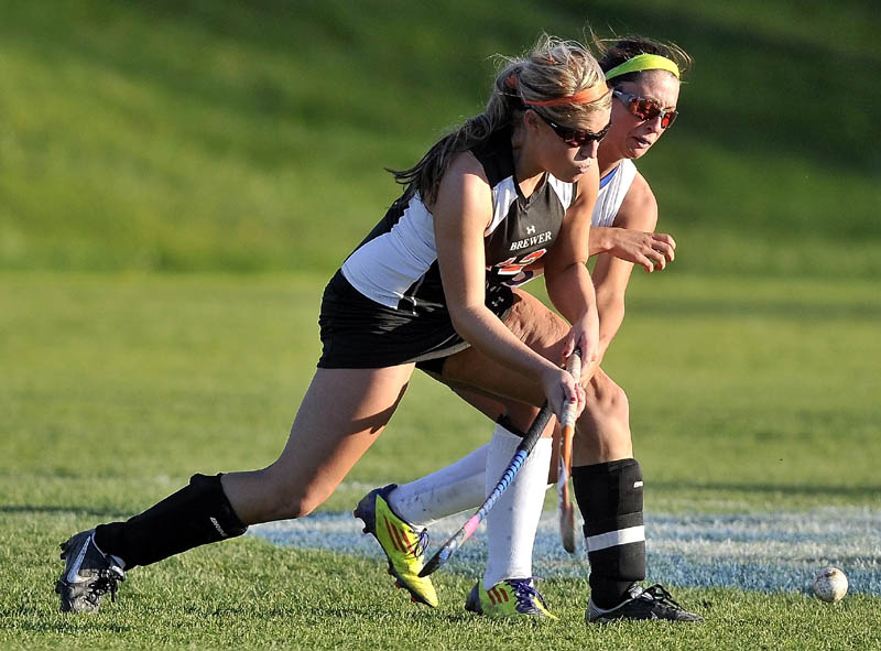 Staff photo by Michael G. Seamans Lawrence High School's Kaprice Dahms, 5, back, fights for the ball with Brewer High School's Rachel Triplett, 12, in the second half of an Eastern A quarterfinals game at Lawrence High School in Fairfield Thursday. Lawrence defeated Brewer 2-1.