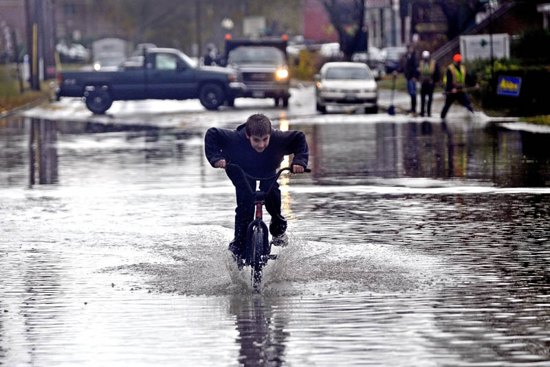 Hunter Desveaux rides his bicycle through floodwater on Front Street, after heavy rain fell on Waterville Tuesday.