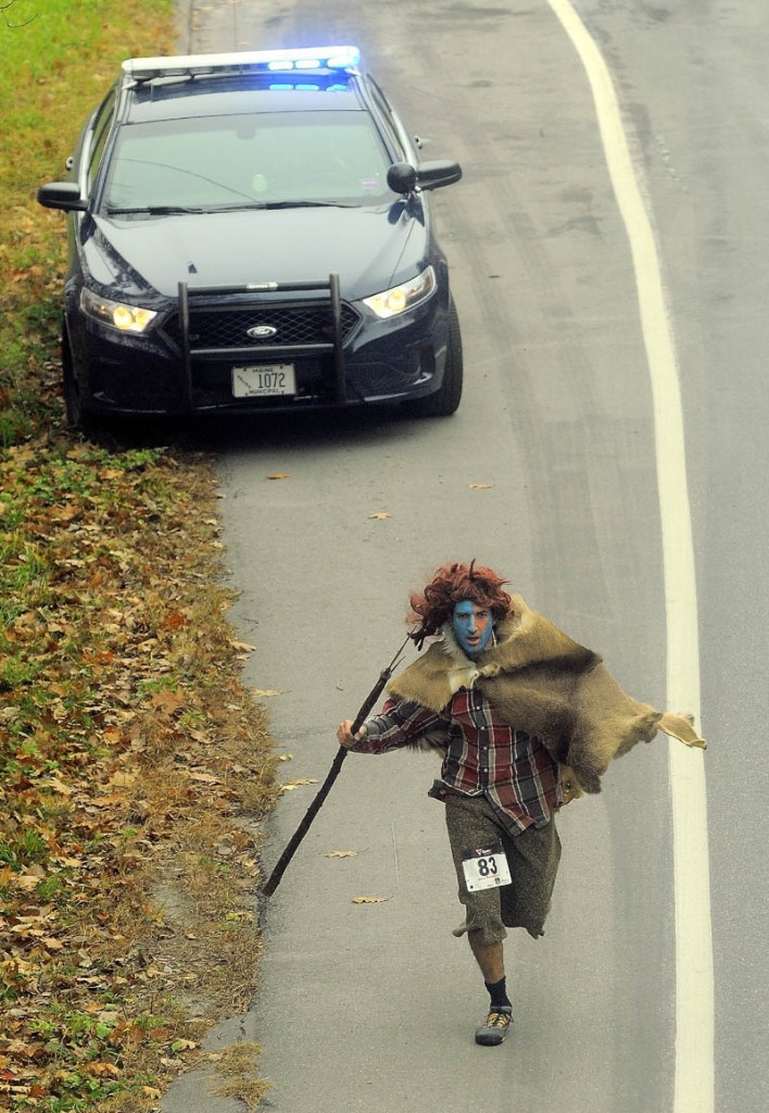 Staff photo by Michael G. Seamans David Gulak, dressed as William Wallace from Braveheart, runs up Mayflower Hill Drive as a Waterville police car watches traffic during the 4th annual Freaky 5k Run and Walk hosted by Hardy Girls Healthy Women and the Colby Volunteer Center at Colby College Saturday morning.