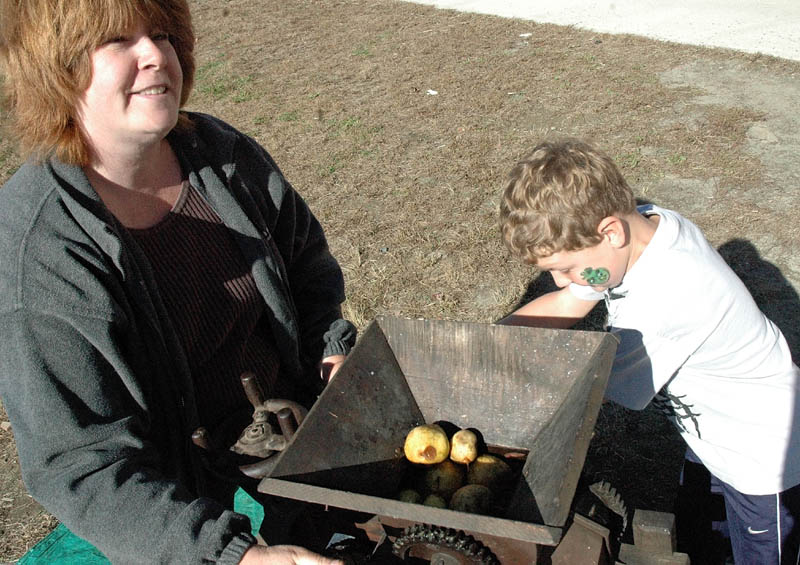 Kim Richards, education technician, and Haden Daigle, 8, make cider with an apple press at the Applefest at the Mill Stream Elementary School in Norridgewock Saturday.