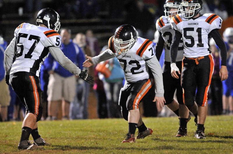 Gardiner High School's defensive lineman Darian Donahue, 72, center, celebrates a tackle with Jory Vermillion, 57, left, in the first half in Madison friday night.