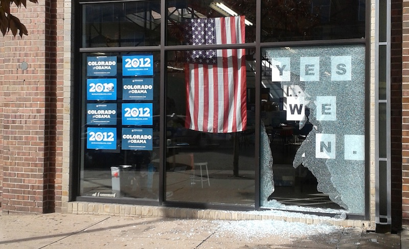 This photo provided by Courtney Grimm shows the shattered glass outside of President Barack Obama's Denver campaign office on Friday, Oct. 12, 2012. Denver police say someone gired a shot through the window of the campaign office while people were inside the office. On Friday, Oct. 19, 2012, someone also spray-painted swastikas on President Barack Obama's campaign office in Conifer, Colo. (AP Photo/Courtney Grimm)
