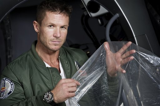 In this Feb. 23, 2012, pilot Felix Buamgartner of Austria shows a piece of the balloon material he will use. It's described as a