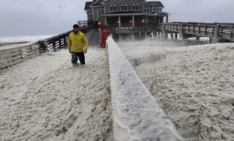 A news crew wades through sea foam blown onto Jeanette's Pier in Nags Head, N.C., on Sunday, as wind and rain from Hurricane Sandy move into the area.