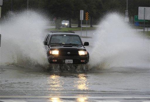 A car plows through a flooded street as rain and wind from Hurrican Sandy hit Norfolk, Va., on Sunday.