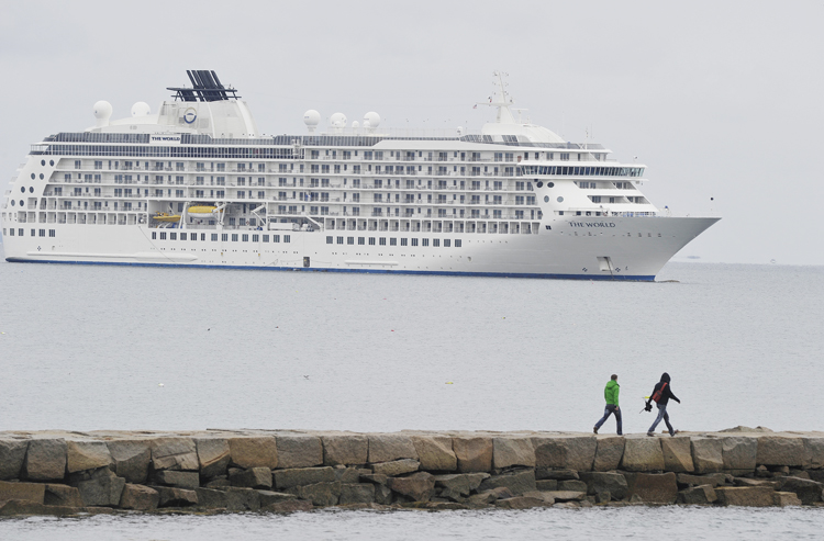 Two hikers walk along the causeway to Rockland Breakwater Light to get a closer look at the 644-foot, privately owned condominium ship The World.