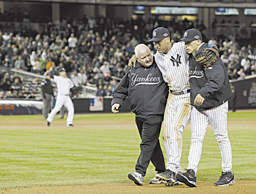 OUCH: Trainer Steve Donohue, left, and New York Yankees manager Joe Girardi, right, help Derek Jeter off the field after he broke his left ankle during Game 1 of the American League Championship Series against the Detroit Tigers early Sunday morning in New York.