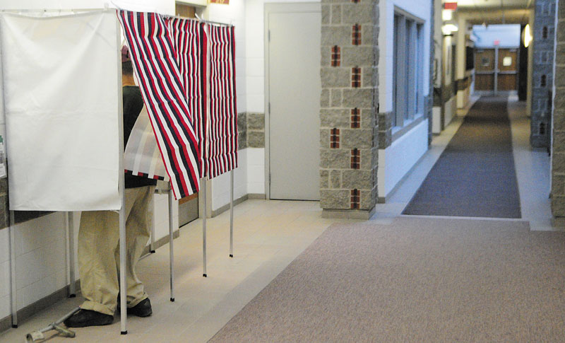 Mike Bradley fills in his absentee ballot in a voting booth in a hallway near the city clerk's office on Thursday morning in Augusta City Center.