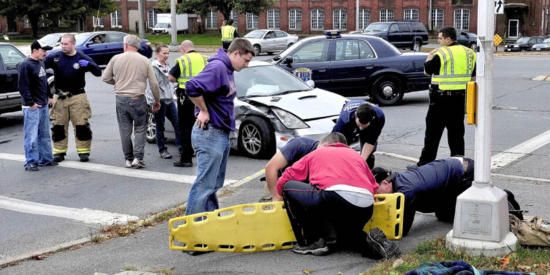 Waterville police and ambulance personel treat injured following an accident at the intersection of Main and Spring Streets in Waterville on Monday.