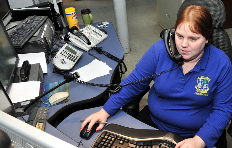 Waterville police dispatcher Sarah Bailey takes an emergency call at the department on Thursday. Earlier, Bailey coached Glenn Adams, of Oakland, through helping his wife, Heather, deliver their son.