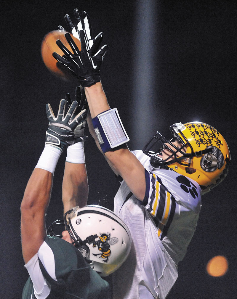 UP AND OVER: Mt. Blue High School receiver Cam Abbott, right, reaches over Leavitt High School defender Brian Bedard for a touchdown on the second play in the first quarter Friday at Leavitt High School in Turner.