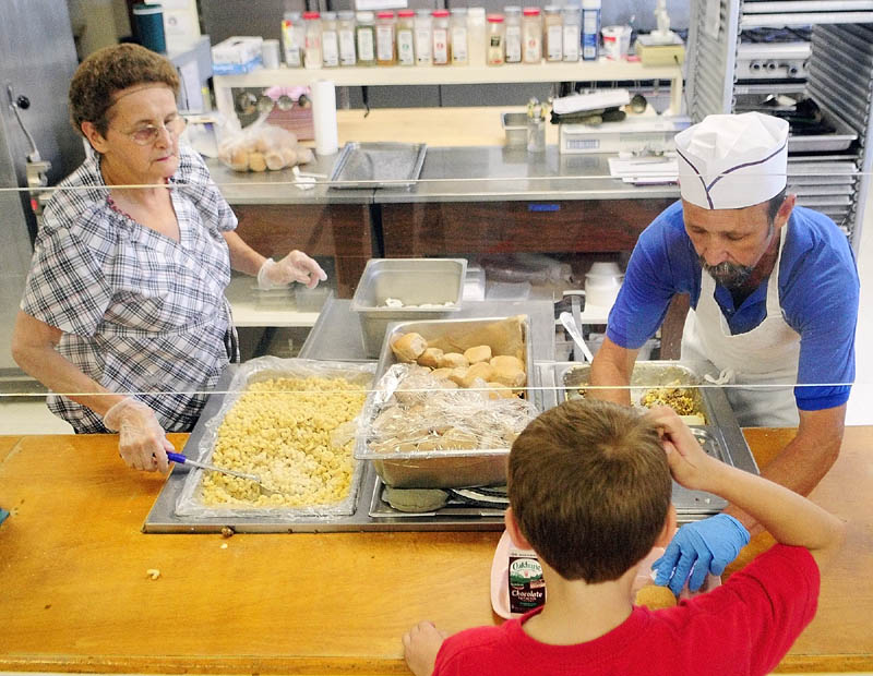 Sharon Nash, left, and Rick McArthur serve up hot lunch, either Shepherd's Pie or Mac & Cheese, to students last week at Pittston Consolidated School.