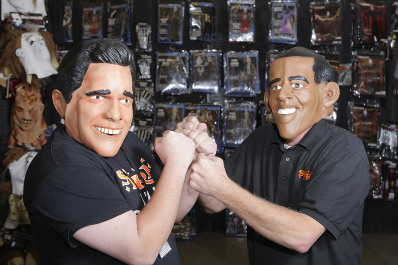 Jeremy Davis and Scott Stevens, employees at Spirit Halloween in South Portland, model masks of Mitt Romney and President Obama. Nationally, Obama was outselling Romney as of last week, says the chain, which claims that sales of such masks have been a successful indicator of presidential preference since 1996.