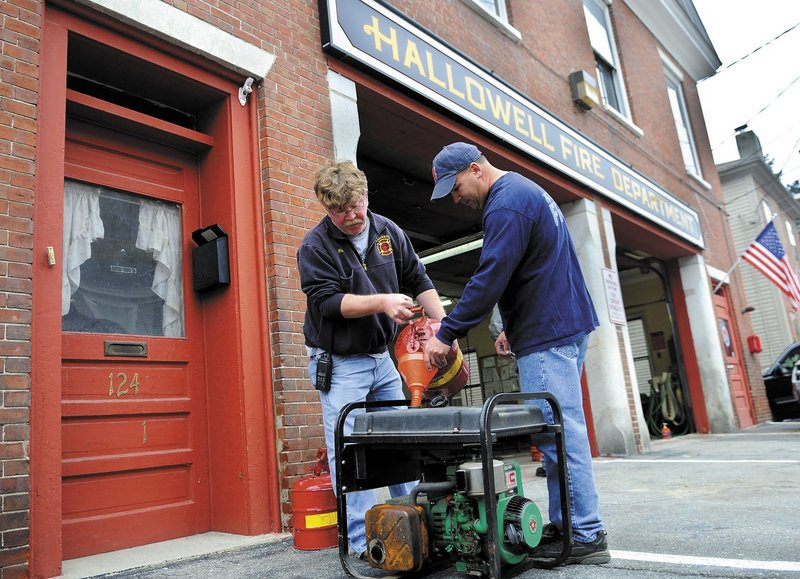 Hallowell firefighters Rick Seymour, left, and Roy Girard fuel up a generator Sunday at the town fire station. The volunteer company was testing emergency equipment and preparing the station for the arrival of storm Sandy, which may disrupt power and cause flooding.