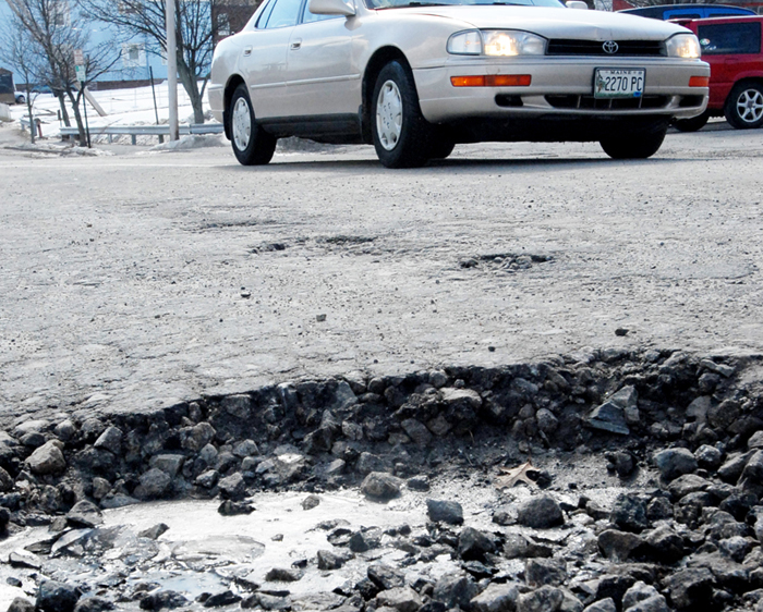 In this 2008 file photo, a vehicle makes its way past a pothole on a section of Chestnut St. in Portland. A new report says Mainers on average pay an extra $300 because of poor road conditions, and it's even worse around Portland.