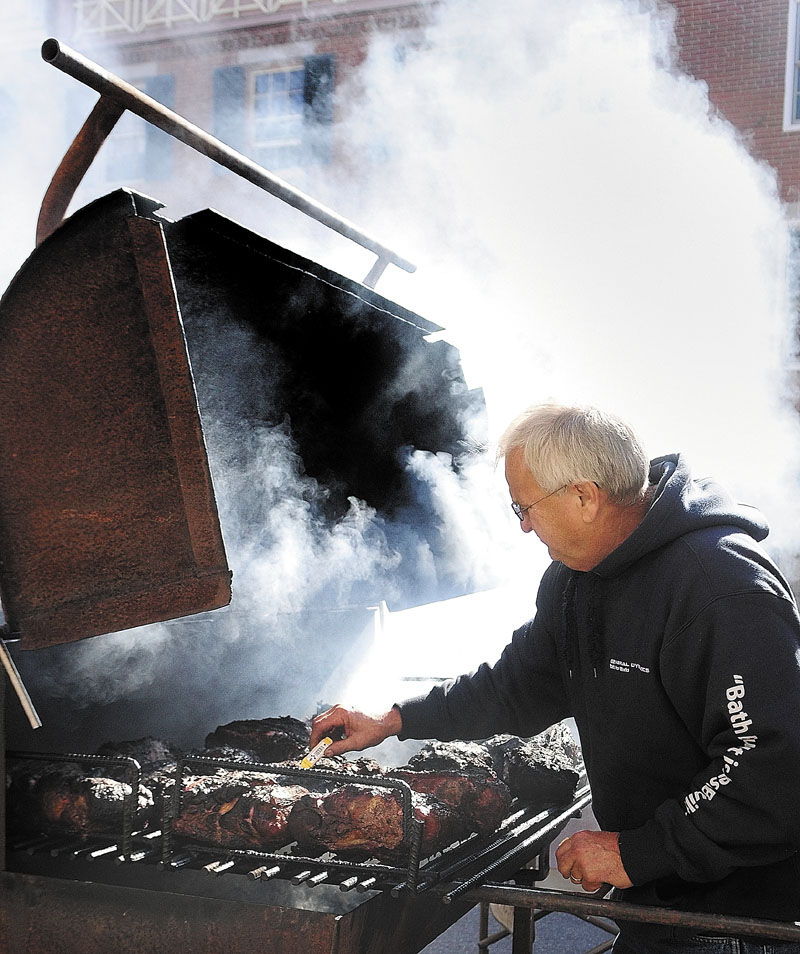 Bob Lutz is shrouded in smoke as he checks the temperature of a Boston Butt he's cooking in front of Gerard's Pizza during the Swine and Stein event on Saturday morning in downtown Gardiner. Lutz said that he would pull the meat when it was at 190 degrees, which should be cooked up moist and falling apart for pulled pork sandwiches. He'd lit the fire at 4:30 a.m. and was cooking the meat at low temperatures for several hours.